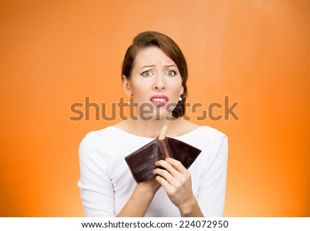 Bankrupt. Portrait sad young unhappy business woman girl holding showing empty wallet isolated orange background. Negative human emotions facial expressions. Financial failure bankruptcy concept  - stock photo