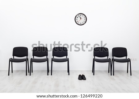 Bankruptcy and business failure concept - deserted chairs and a pair of shoes - stock photo