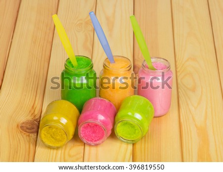 Banks of various baby food and spoons on a background of light wood. - stock photo