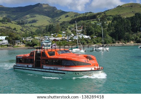 BANKS PENINSULA, NEW ZEALAND, DECEMBER 22, 2011 - A ferry carries people to a cruise ship in Akaroa Harbour since Christchurch port was damaged by earthquake; Banks Peninsula, New Zealand, 22-12-2011 - stock photo