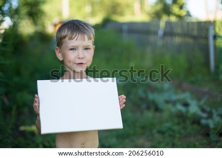 Banner is for your message: Little boy holding clean white sheet paper, near a country house. - stock photo