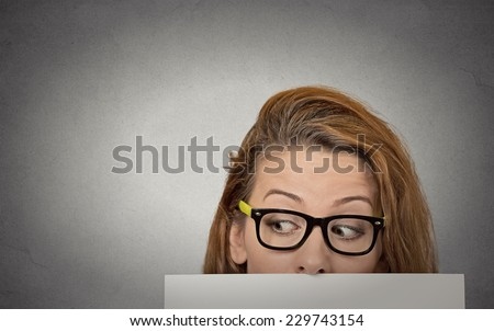 Banner sign woman peeking over edge of blank empty paper billboard. Beautiful young girl with glasses looking to side surprised curious scared funny interested open eyes isolated grey wall background - stock photo