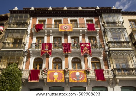 Banners with historical emblems hang from windows of an old building in the Plaza de Zocodover in Toledo, Spain