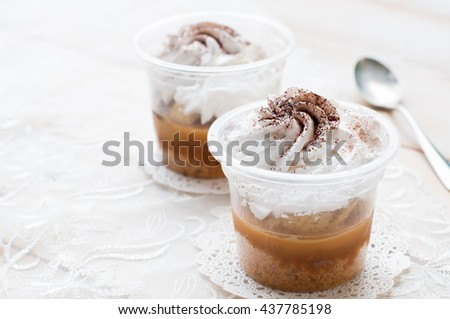 banoffee pie in a cup, spilled with caramel and whipped cream, delicious dessert. - stock photo