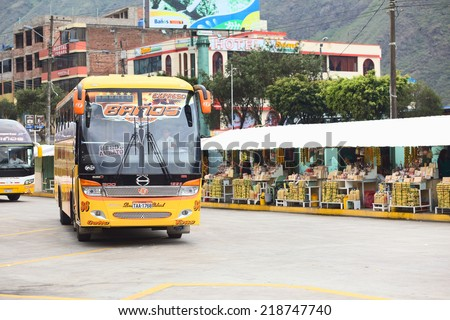 BANOS, ECUADOR - FEBRUARY 22, 2014: Bus of the Expreso Banos transportation company in the bus terminal with a row of small sweets stands in the back on February 22, 2014 in Banos, Ecuador.  - stock photo
