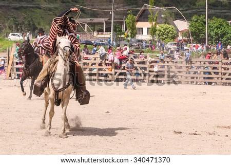 Banos, Ecuador - 30 November 2014: Young Courageous Cowboy Riding A Horse And Throwing A Lasso, South America In Banos On November 30, 2014 - stock photo