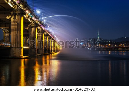 Banpo Bridge Rainbow Fountain show on han river taken at night. Seoul famous landmark, with the view of seoul N tower. South Korea.
