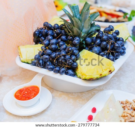 Banquet table served with delicious food. Fresh grapes, pineapple and walnuts on the plate - stock photo
