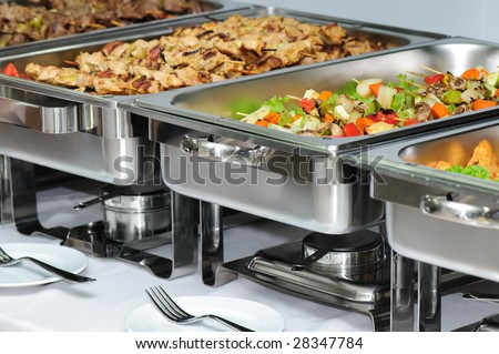 banquet table with chafing dish heaters - stock photo