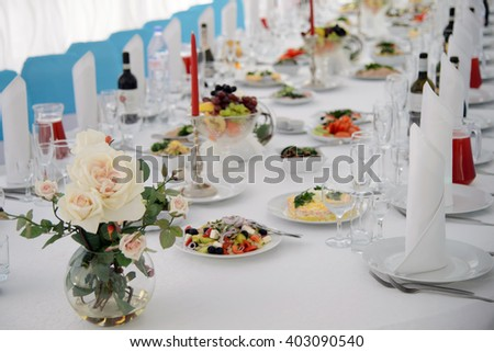 Banquet table with Cutlery and tableware.  Festive table with food for a celebration. Table with white tablecloth served to guests. The table in the restaurant. Luxury Desk for the celebration. - stock photo