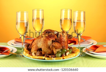 banquet table with roasted chicken on orange background close-up. Thanksgiving Day