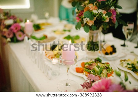 Banquet wedding table setting on evening reception awaiting guests with candle - stock photo