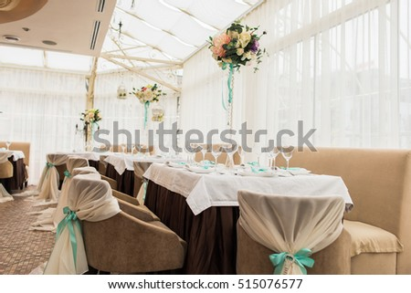 banqueting hall. serving table. decorated wedding chairs in row. wedding luxury party place. restaurant interior