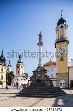 Banska Bystrica, Slovakia - august 07, 2015: Old Castle with clock tower on sunny day. Barbican. Holy sculpture on the column