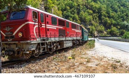 Bansko, Bulgaria -29 July 2016: Small retro rock train moves through the old narrow-gauge rails worn winding mountain road past the railway passenger station along the ridge