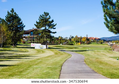 Bansko, Bulgaria - October, 31, 2015: Pirin Golf Club house and restaurant, colorful autumn trees, path, green grass field, blue sky