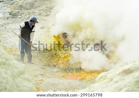 BANYUWANGI, EAST JAVA JULY 20 : Sulphur miner points to hardened sulphur from the ground to be collected and sold on July 20, 2013, Ijen volcano, East Java, Indonesia.