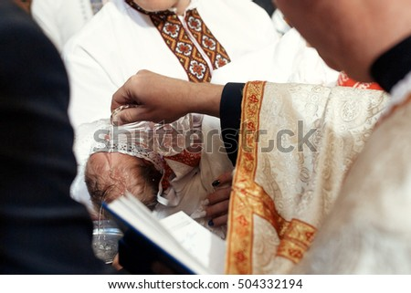 baptism baby. cute little head of a girl under holy water at christening ceremony with priest in church of a girl under holy water at christening ceremony with priest in church and bible