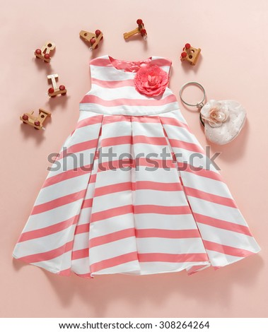 baptism girl clothes and accessories toys in plan on a salmon color - stock photo
