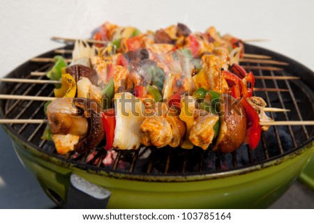 Bar-B-Q or BBQ with kebab cooking. coal grill of chicken meat skewers with mushroom and peppers. barbecuing dinner - stock photo