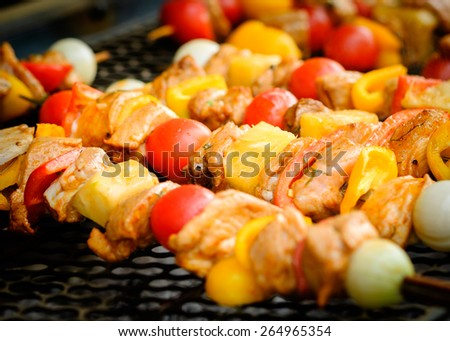 Bar-B-Q or BBQ with kebab cooking. Coal grill of pork skewers with tomatoes, onion and peppers. barbecue camping dinner. - stock photo