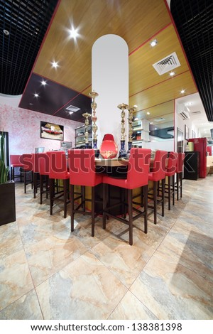 Bar counter with tall red chairs in hall of cozy Japanese restaurant.