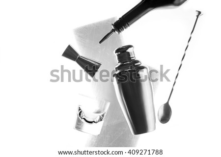 Bar equipment on stripes under scratched ice isolated on white background. Bar spoon, shaker, pourer on a black bottle and old-fashioned glass. Black and white