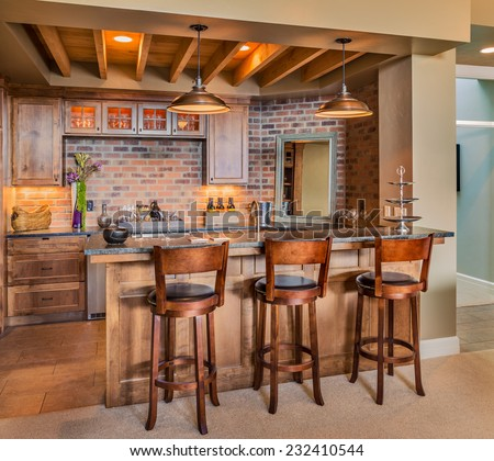 Bar in new luxury home, complete with chairs wine glasses, beer, and new cabinets - stock photo