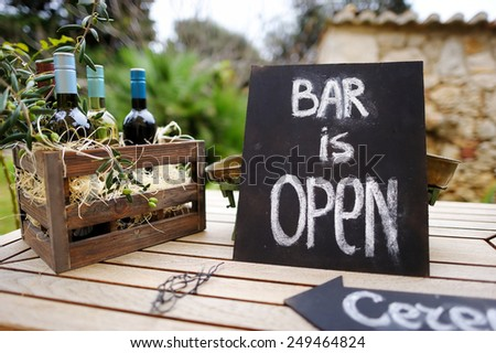 Bar is open sign and vintage wooden crate full of wine bottles decorated with olive branches on a table - stock photo