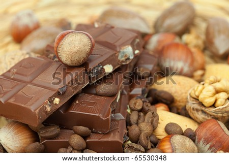 bar of chocolate and nuts on a wicker mat - stock photo