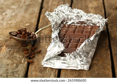 Bar of chocolate in foil with coffee beans in spoon on wooden table - stock photo