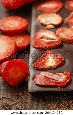 Bar of chocolate with dried strawberries - stock photo