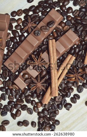 bar of dark chocolate, milk chocolate bar, coffee beans, star anise, cinnamon sticks, seasonings, spices, close-up on a white wooden background - stock photo