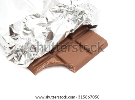 bar of milk chocolate in a foil on white - stock photo