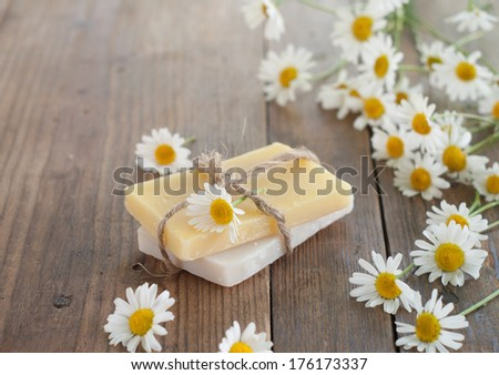 Bar of natural handmade soap and chamomile on wooden background. Selective focus.