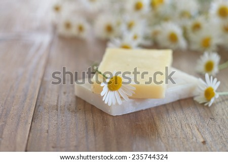 Bar of natural handmade soap and chamomile on wooden background. Selective focus. - stock photo
