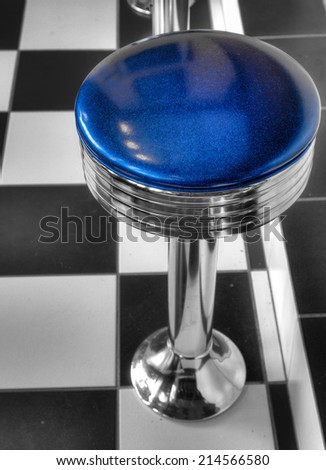 Bar stool with blue seat against checkered floor - stock photo