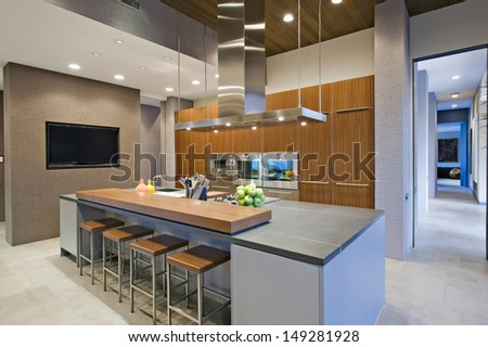 Bar stools at breakfast bar in contemporary kitchen - stock photo