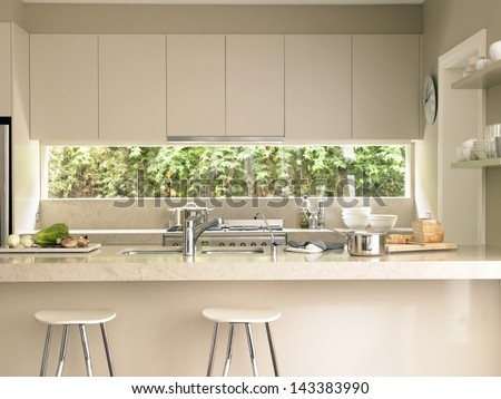 Bar stools by modern kitchen island - stock photo