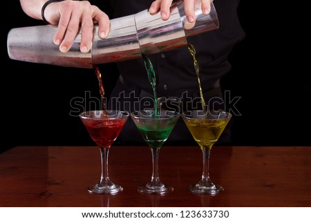 bar tender pouring three different color martinis in one fluid motion - stock photo