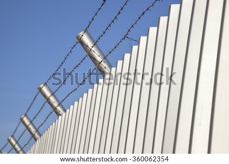 Barb wire fence and blue sky blackground