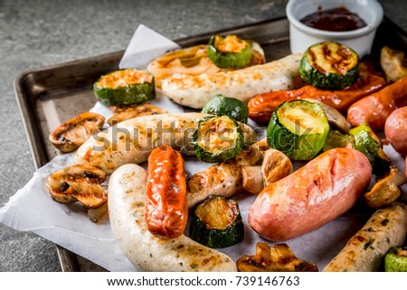 Barbecue. Assortment of various grilled meat sausages, with vegetables BBQ - mushrooms, tomatoes, zucchini, onions. On a black stone table, on a baking sheet, with sauce. Copy space