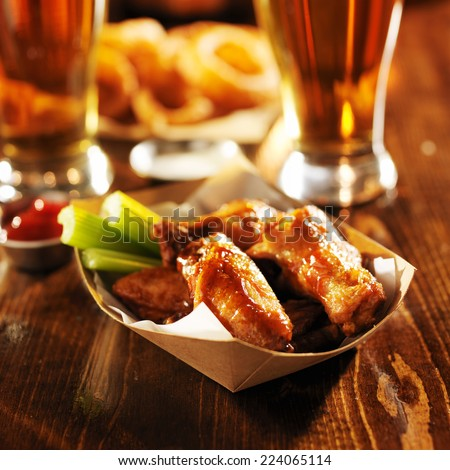 barbecue buffalo chicken wings served with beer, celery, and ranch in basket - stock photo