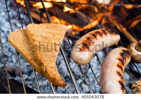 Barbecue grill. Fried sausages. BBQ with fiery sausages on the grill. - stock photo