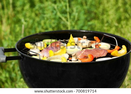 Barbecue grill with meat and vegetables outdoors, close up