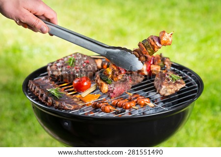 Barbecue grill with various kinds of meat. Placed on grass. - stock photo
