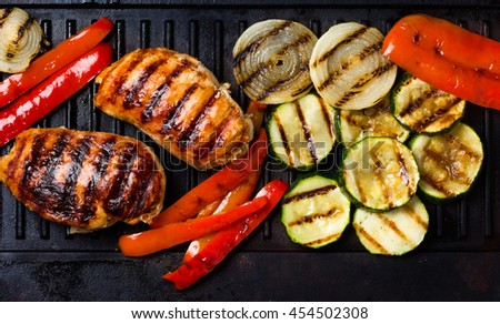 Barbecue grilled chicken and vegetables - zucchini, bell pepper, onion and barbecue sauce on cast iron black table for grill. Top view