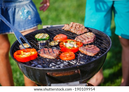 Barbecue on a hot day during the summer vacation on a green grass background. Meat and vegetables on the grill. - stock photo