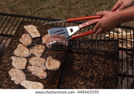 Barbecue pork chops and chicken on a hot granite countertop. Summer party with barbecue. Grilling on a hot stone. - stock photo