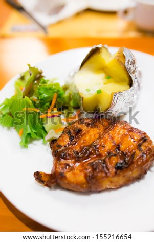 Barbecue pork steak in plate with potato and salad